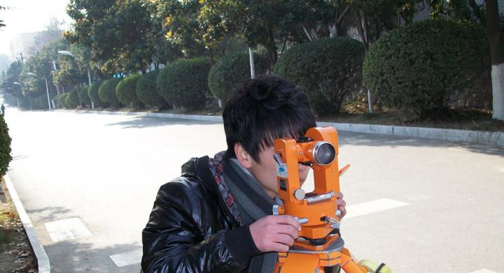 Surveyor at work in residential area.